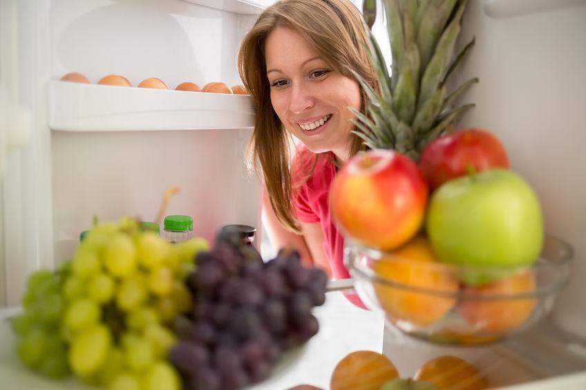 Imagem do interior da geladeira com moça pegando ingredientes