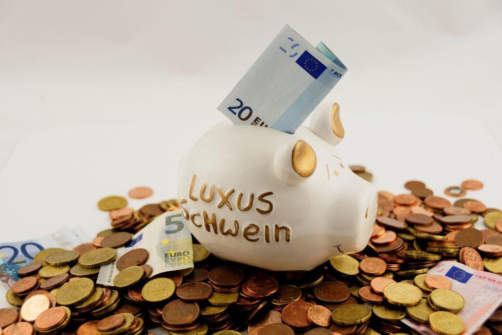 Um cofrinho em forma de porco na cor branca com detalhes dourados está em cima de uma montanha de moedas e notas de euro. Uma nota de 20 euros está na abertura para inserção de dinheiro do cofrinho.