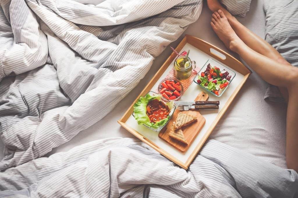 Pernas de moça estendidas na cama ao lado de bandeja com alimentos.