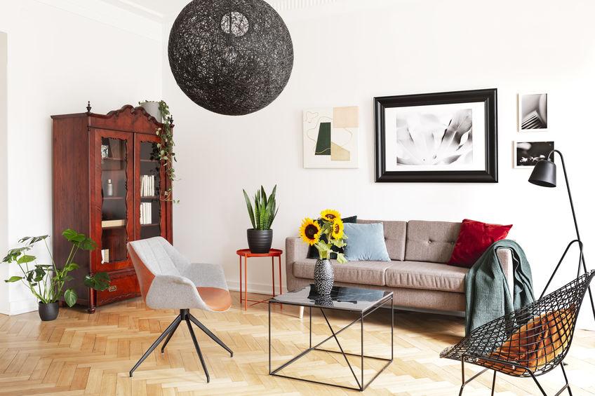 Imagem de uma sala de estar em estilo moderno com uma cristaleira colonial ao fundo.