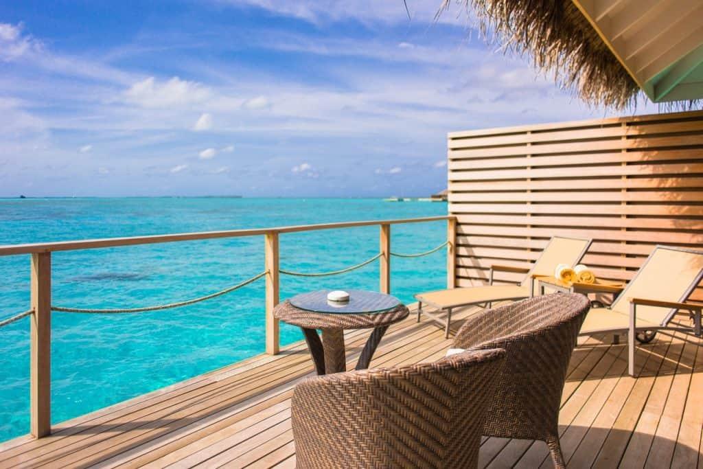 Imagem de cadeiras de jardim e mesa em frente ao mar.