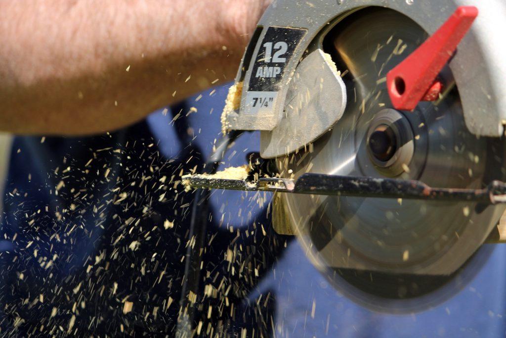 Imagem mostra uma serra circular em ação e pequenas raspas de madeira no ar.