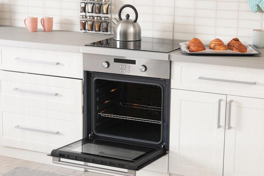 Na foto um forno aberto dentro de uma cozinha.