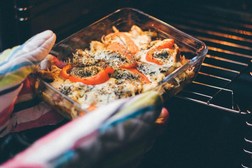 Imagem de pessoa retirando uma bandeja de comida do forno
