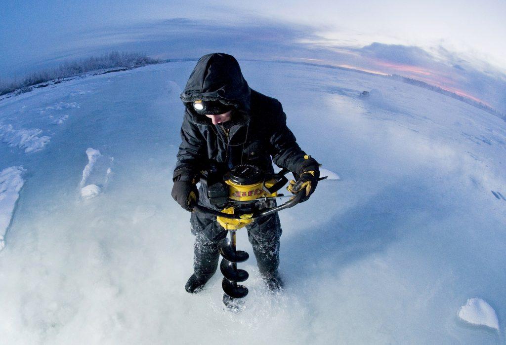 Imagem mostra uma pessoa usando uma perfuratriz em uma superfície congelada.