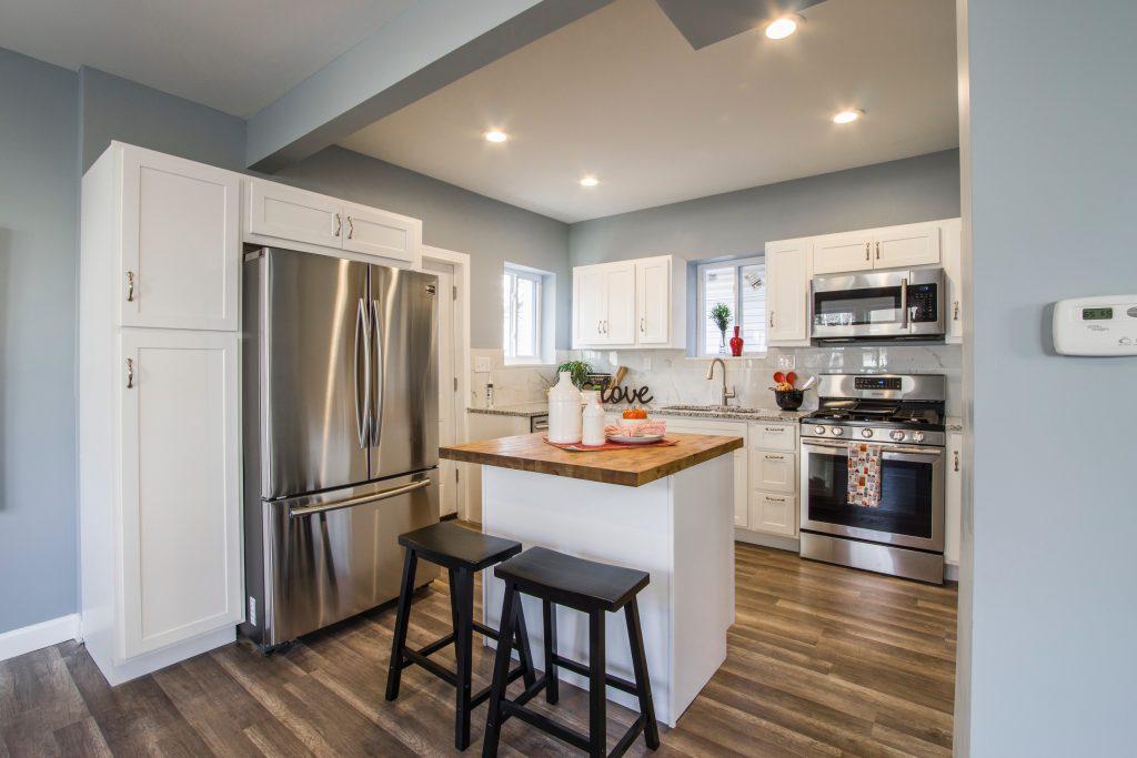 Cozinha branca com ilha e geladeira French Door.