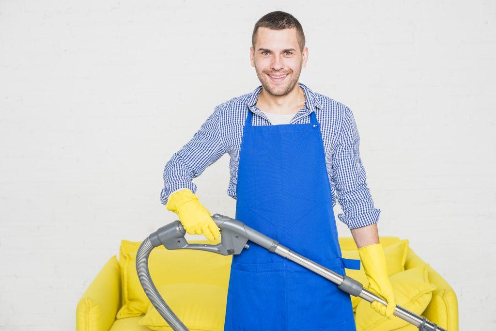 Homem sorri para foto segurando cano do aspirador de pó