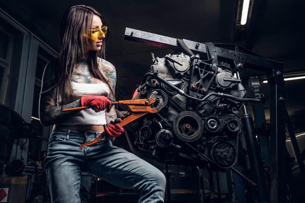 Imagem mostra uma mulher consertando partes de um carro suspensas em um guincho hidráulico.