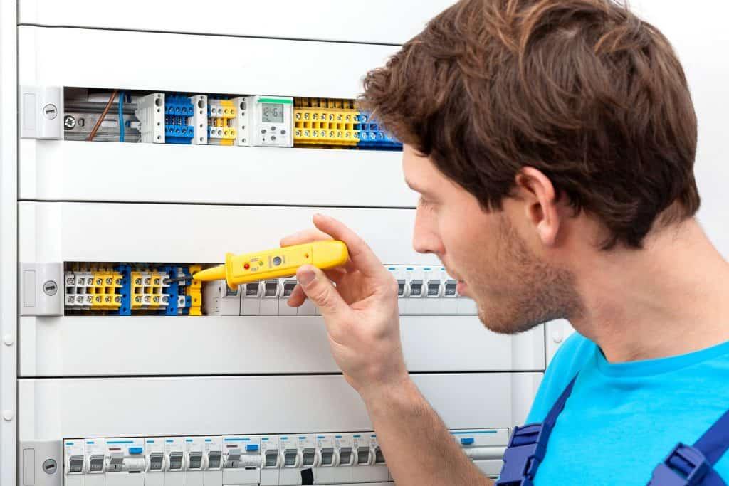 Homem usando um detector de tensão em um painel elétrico.