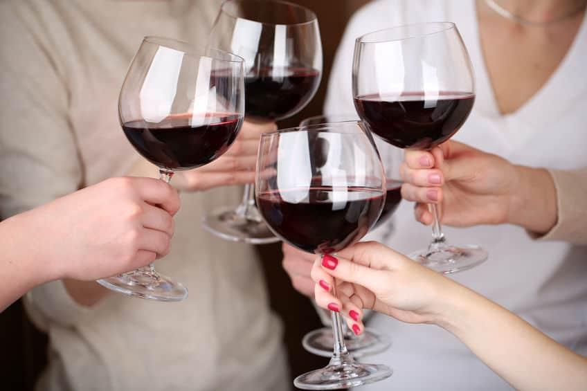 Close da mão de amigos brindando com vinho.