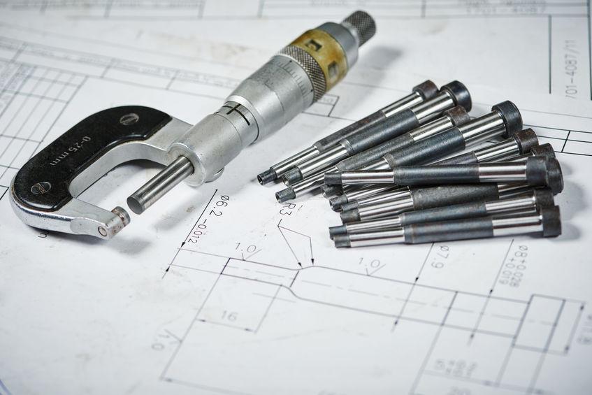 Imagem mostra uma composição com um micrômetro interno de dois contatos com peças metálicas ao seu redor .