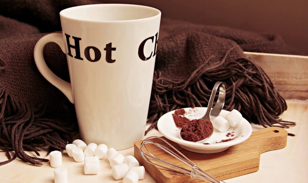 Na foto uma caneca branca, com marshmallows, chocolate em pó e um fouet de inox.