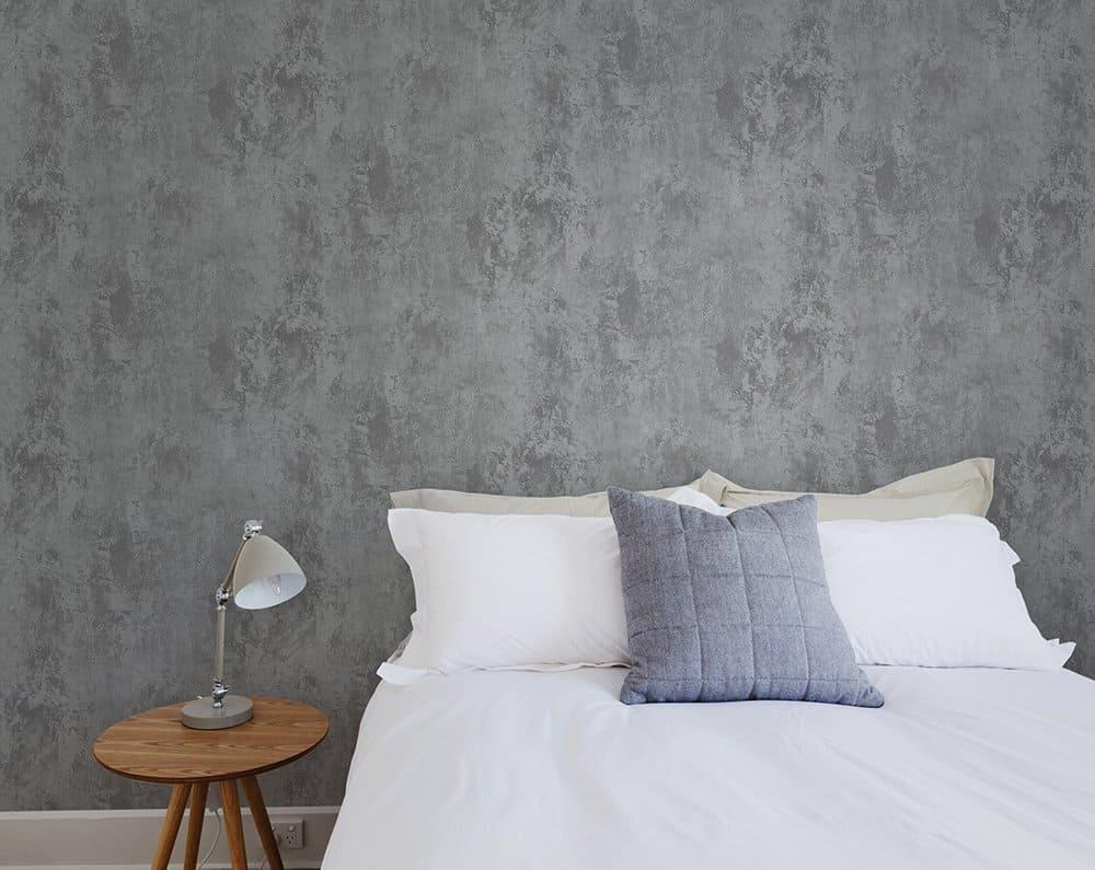 Cama de casal, criado mudo e papel de parede de cimento queimado ao fundo.
