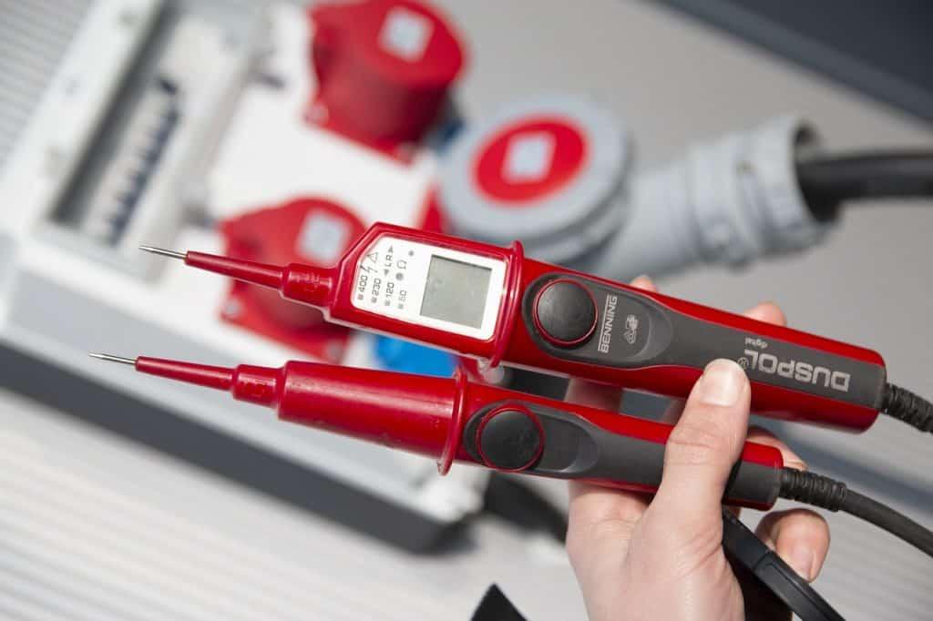 Imagem de uma pessoa segurando um detector fora de uso, com um pequeno quadro de energia desfocado ao fundo.