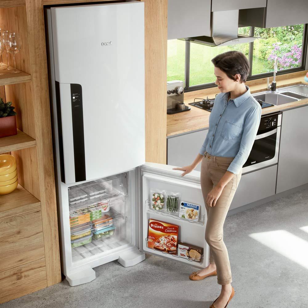 Mulher com porta do freezer embaixo aberta.