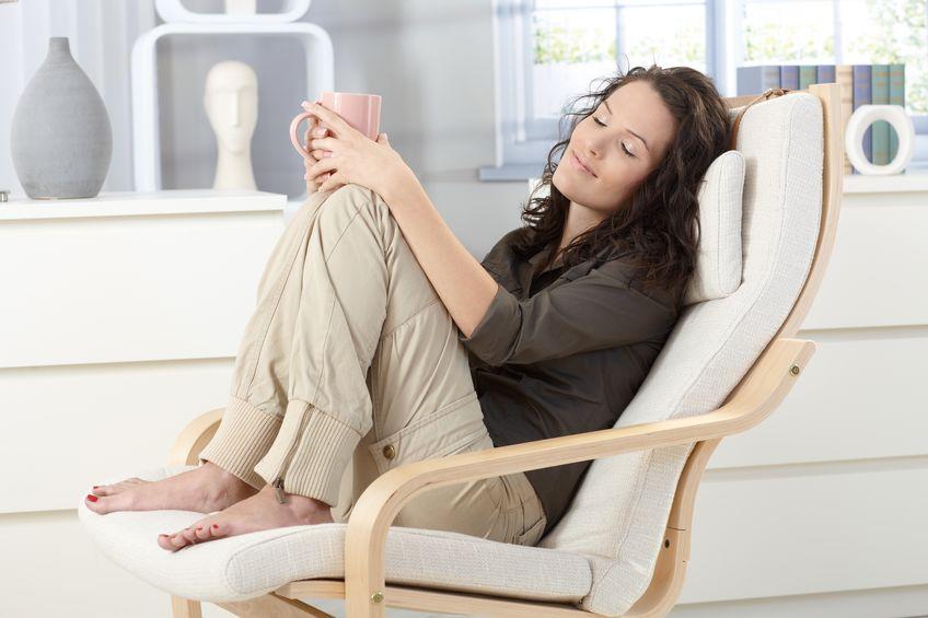Imagem de uma mulher sentada confortavelmente em uma cadeira acolchoada enquanto segura uma xícara de café.