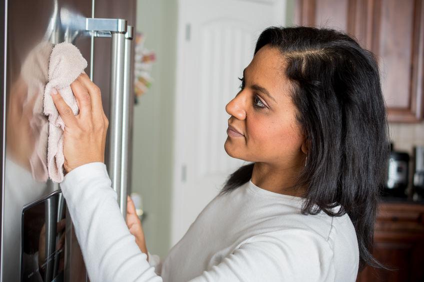 Imagem de mulher limpando sua geladeira inox
