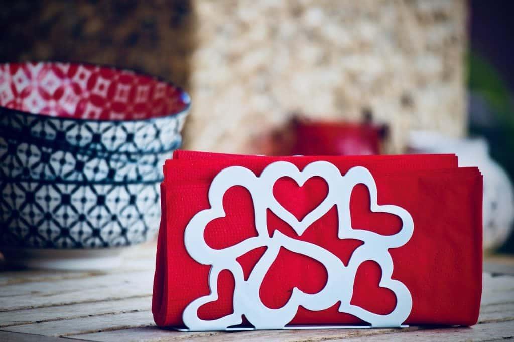 Imagem mostra um porta guardanapo do tipo vertical, com seis corações vazados formando a parede. Ao fundo, potes tigelas coloridas repousam desfocadas sob uma mesa de madeira.