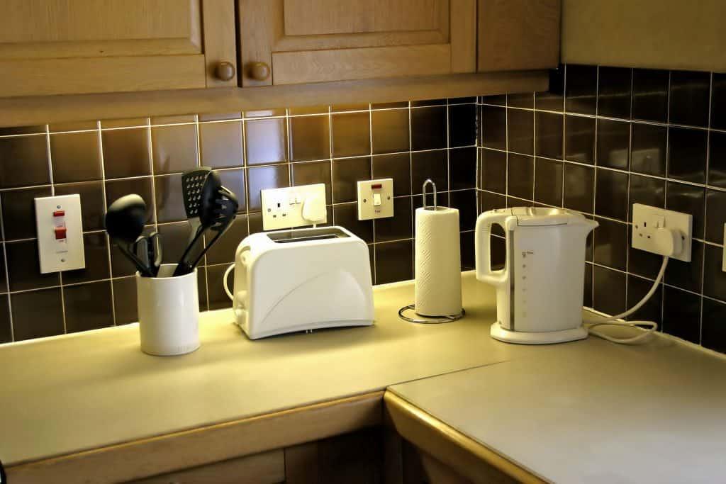 Um balcão de cozinha contendo um porta objetos, torradeira, porta papel toalha e uma chaleira elétrica.