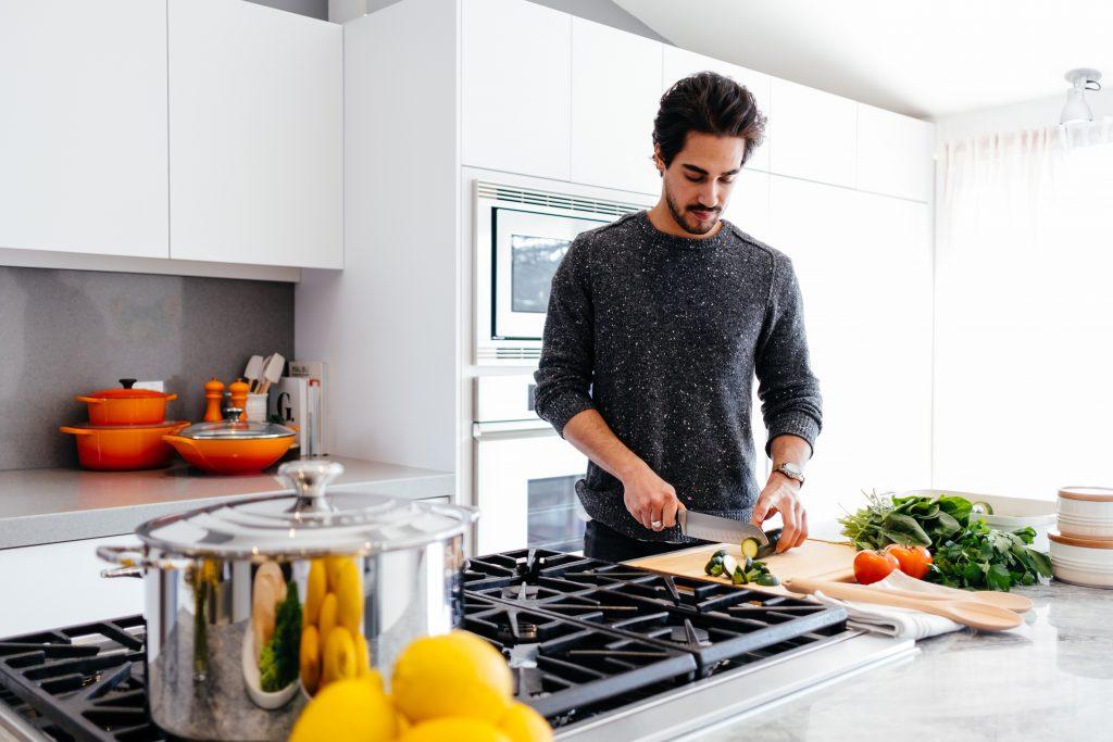 Imagem de um homem cozinhando.
