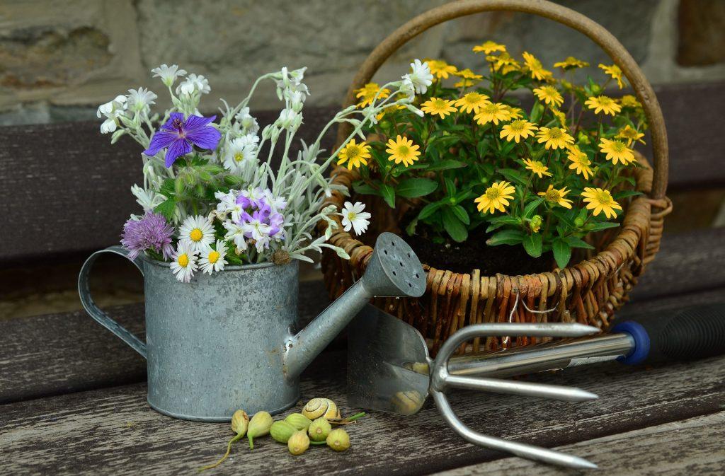 Na imagem um regador prata com flores brancas e roxas ao lado de uma cesta de vime com flores amarelas.