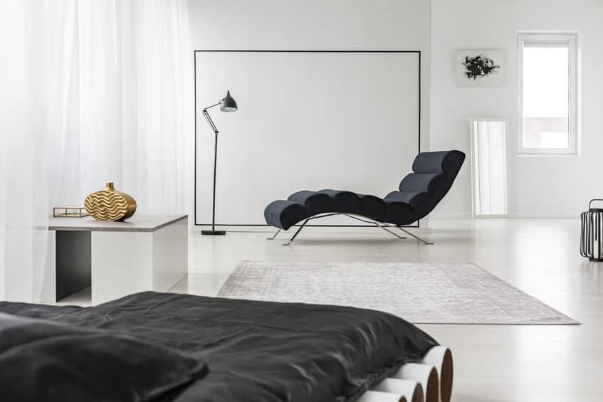 Imagem de divã cinza em cômodo.
