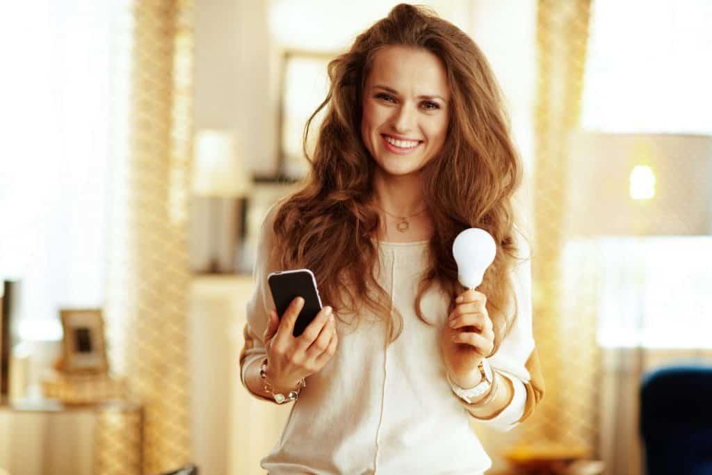 Na foto uma mulher segurando em uma mão um celular e na outra uma lâmpada.