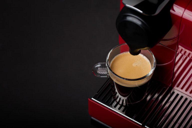 Máquina de café em cápsula com xícara de café preto.