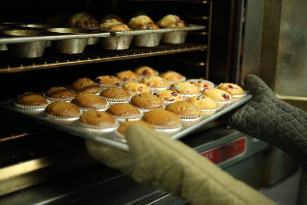 Na foto uma pessoa tirando uma forma com cupcakes de dentro de um forno.