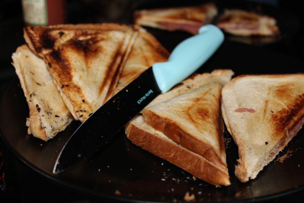 Imagem de sanduiches cortados e faca com cabo azul