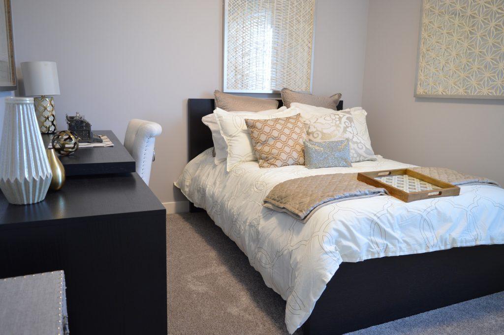 Cama arrumada com almofadas, travesseiros e um edredom claro. Ao lado, há uma escrivaninha com objetos decorativos.