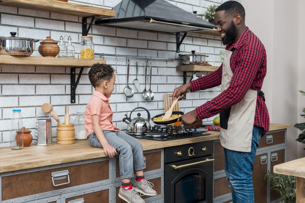 Pai cozinha enquanto filho observa sentado na bancada