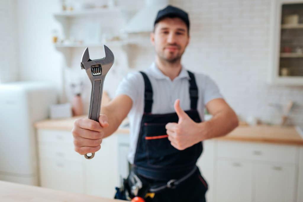 Um operário de macacão e boné com uma chave inglesa em uma das mãos.