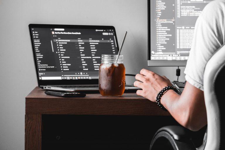 Imagem de uma pessoa trabalhando enquanto consome uma bebida no copo com canudo.