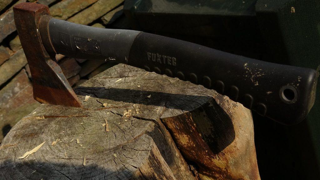 Um machado médio com empunhadura de borracha fincado em um pedaço de lenha