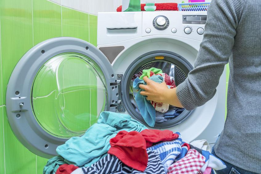 Mulher colocando roupas na máquina de lavar.