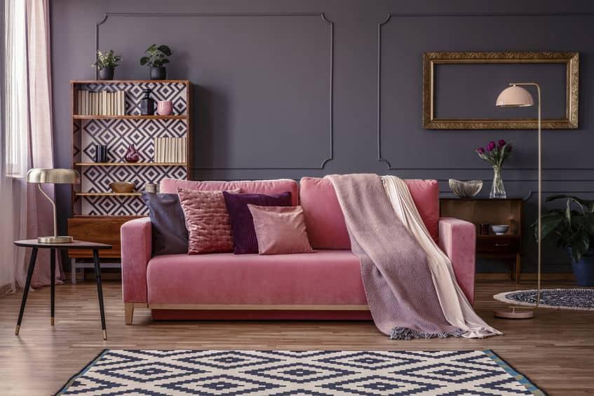 Sala de estar moderna com sofá rosa e mesa de canto e madeira ao lado.