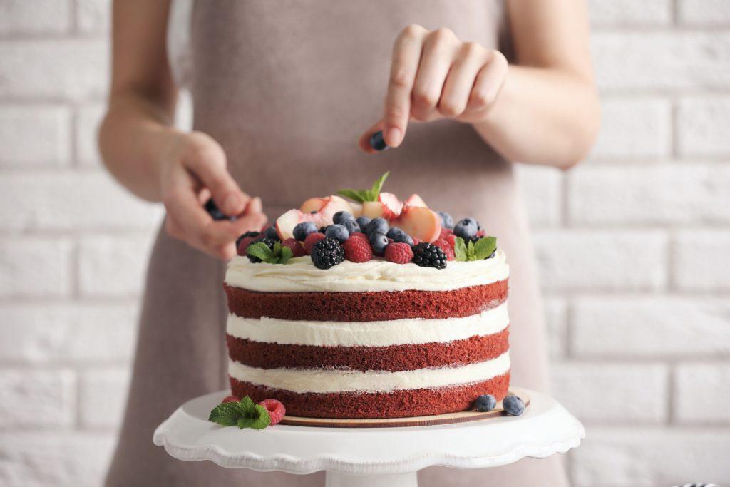 Mulher decorando bolo com frutas.