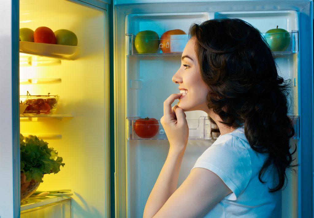 Mulher olhando para dentro da geladeira.