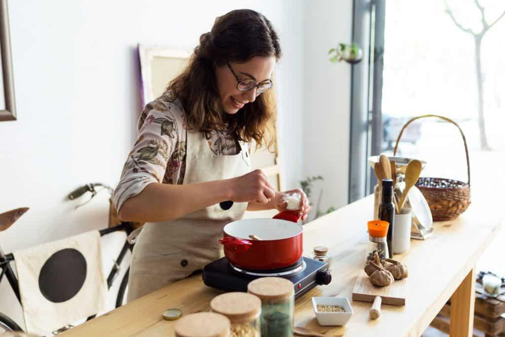 Imagem de uma mulher na cozinha temperando a panela com sal.