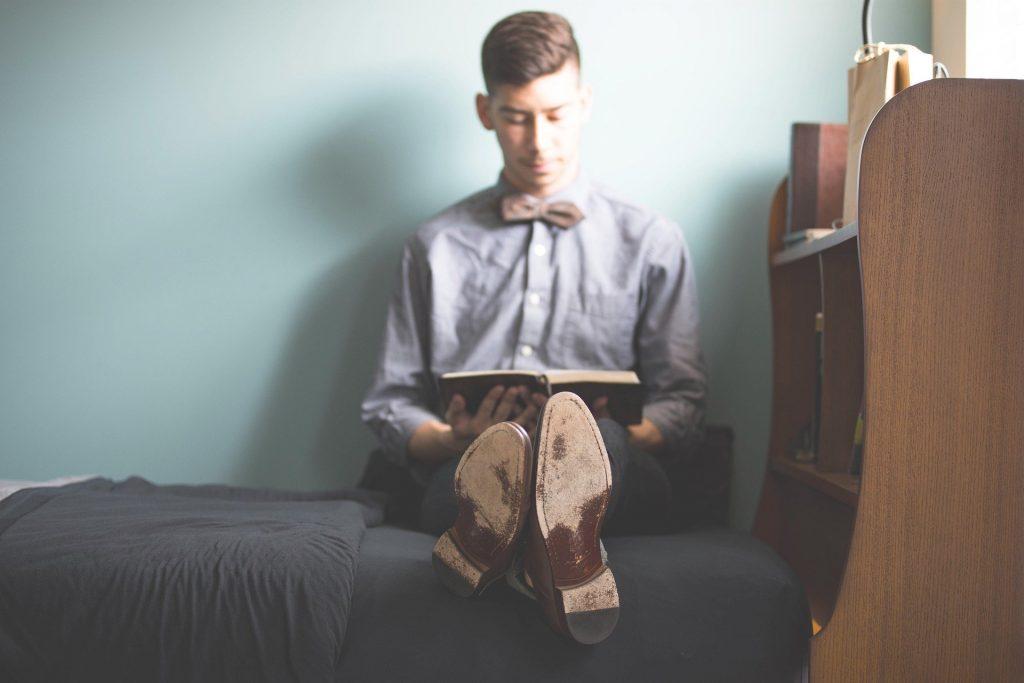 Imagem homem sentado em cama de solteiro enquanto lê um livro