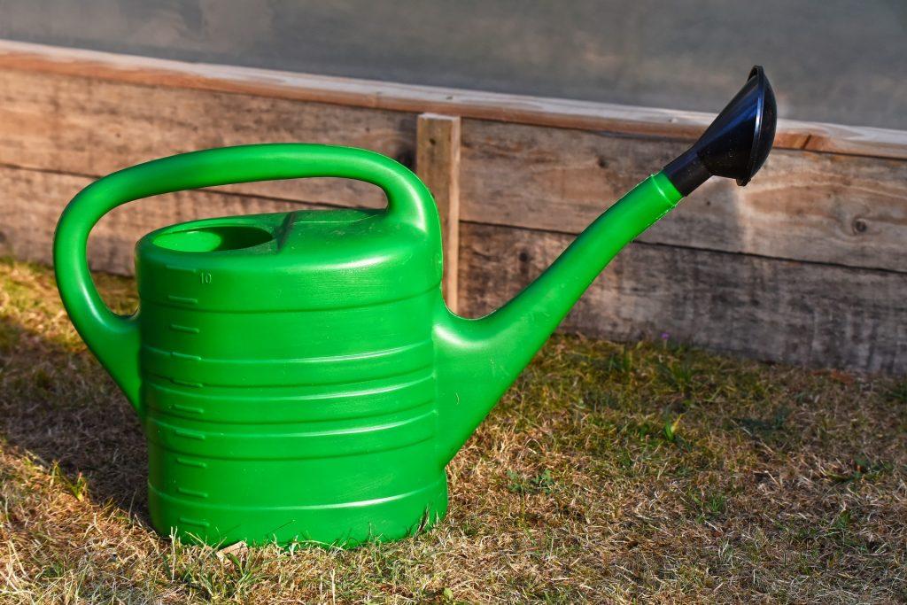 Na imagem um regador verde no gramado.