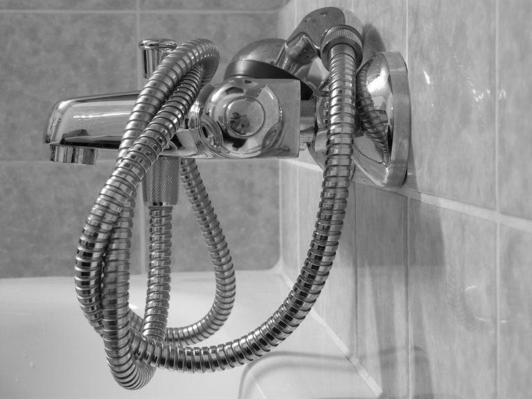 Na foto um chuveirinho enrolado em uma torneira.