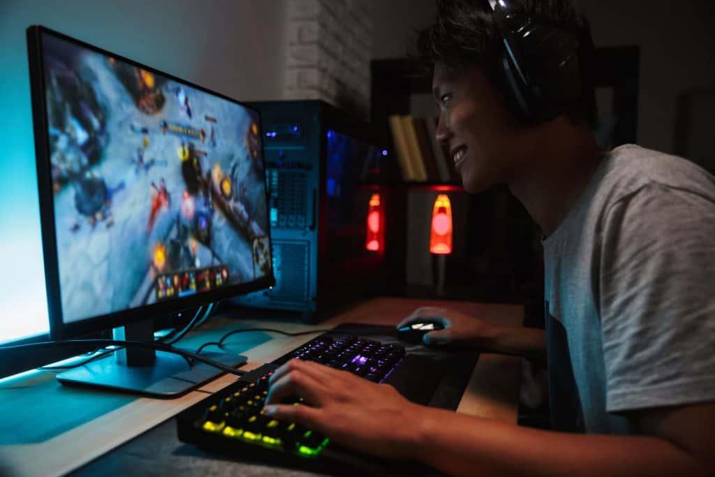 Na foto um jovem jogando vídeo game com um fone de ouvido em frente a um computador.