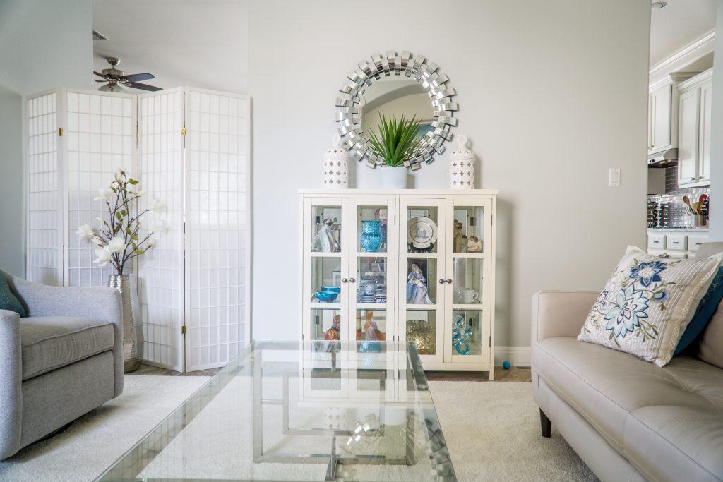 Imagem de uma sala com uma cristaleira ao centro.
