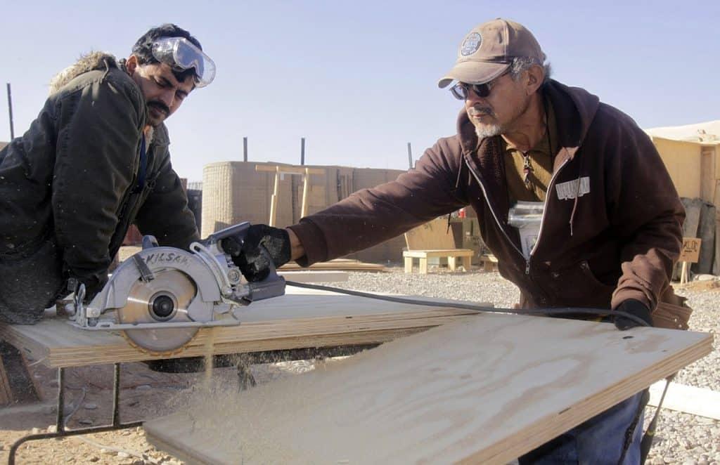 Um homem usa uma serra elétrica para cortar uma tábua de madeira enquanto outro homem observa o trabalho de perto.