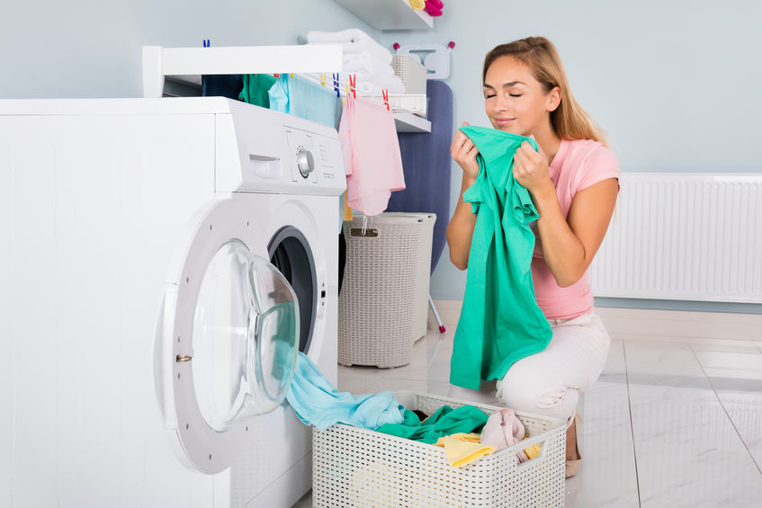 Na foto uma mulher em frente a uma máquina de lavar segurando uma blusa.