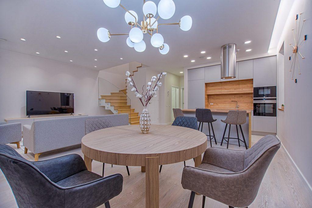 Na foto uma casa com mesa de jantar, sala de estar e cozinha estilo americana.