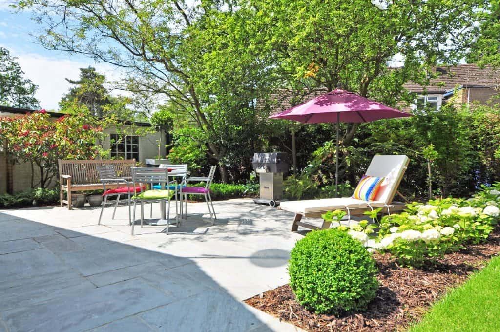 Na foto um jardim de uma casa com bancos, esteira e uma mesa.