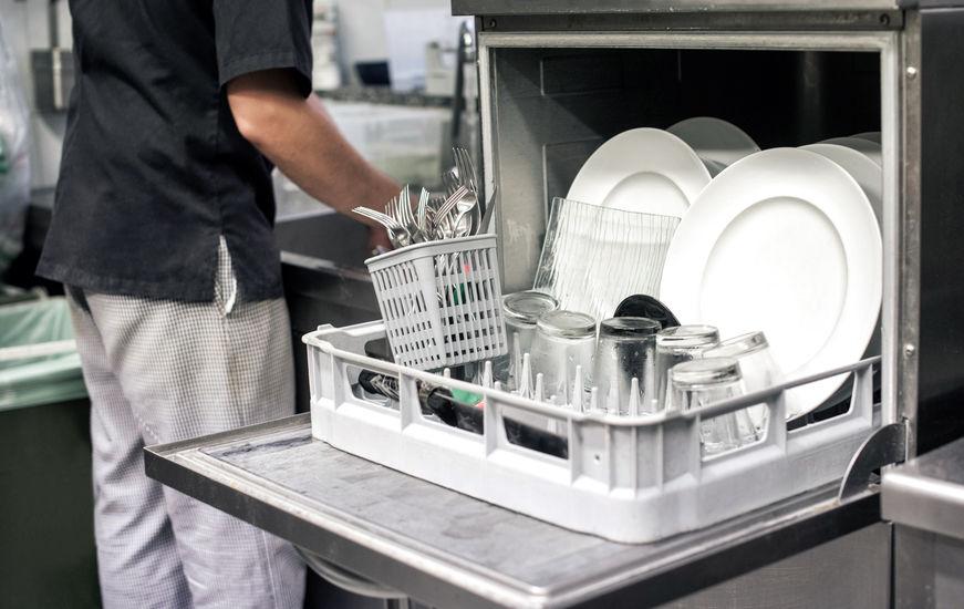 Imagem de uma lava louças aberta com louças dentro e pessoa ao lado.